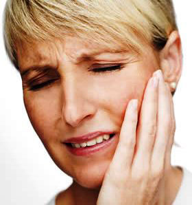 A woman holding her jaw from TMJ pain