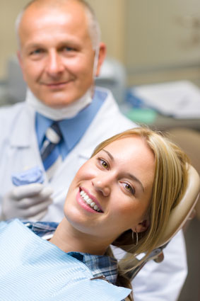 a woman smiling from the dentist chair with her dentist smiling beside her