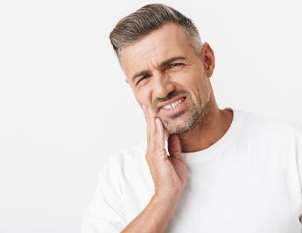 Man holding the side of his face in need of root canal treatment to avoid the need for a dental implant